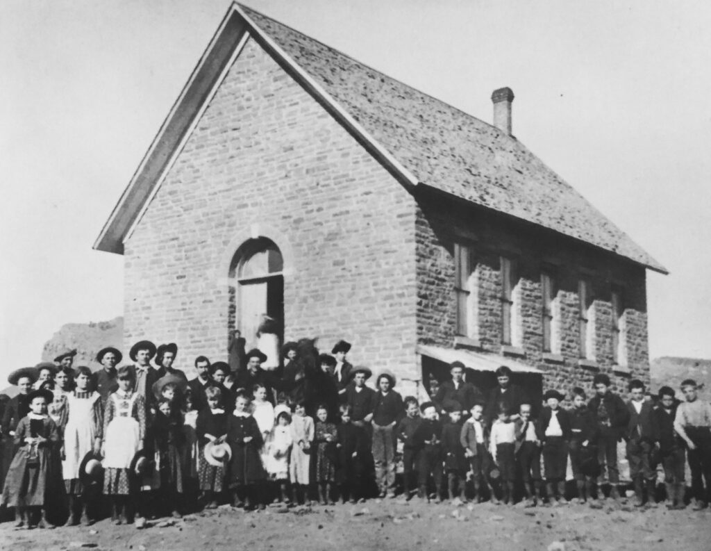 Black and white photograph of the schoolhouse in Lyons, Colorado with schoolchildren lined up in front of the building.