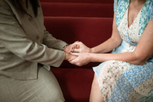 woman in suit hold hands w/woman in sundress, on red stair - blessing