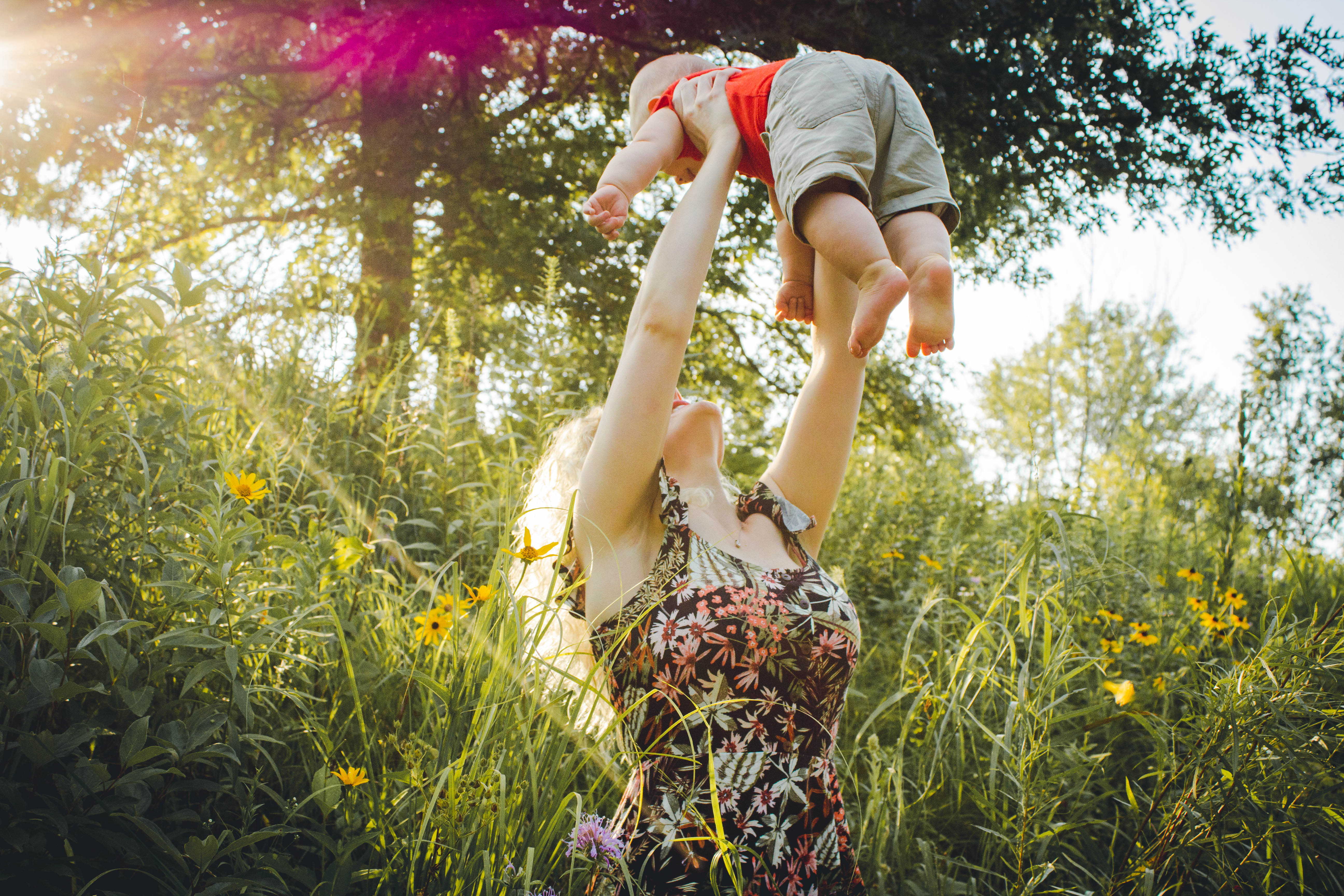 woman holding up baby in air, in field of flowers