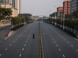 lone man walking on city street with skyscrapers (Loas)