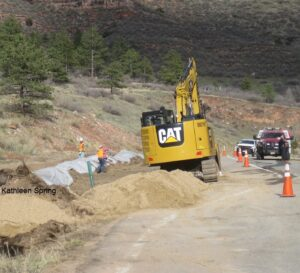 excavator/bulldozer moving materials at site of tanker accident, by Kathleen Spring